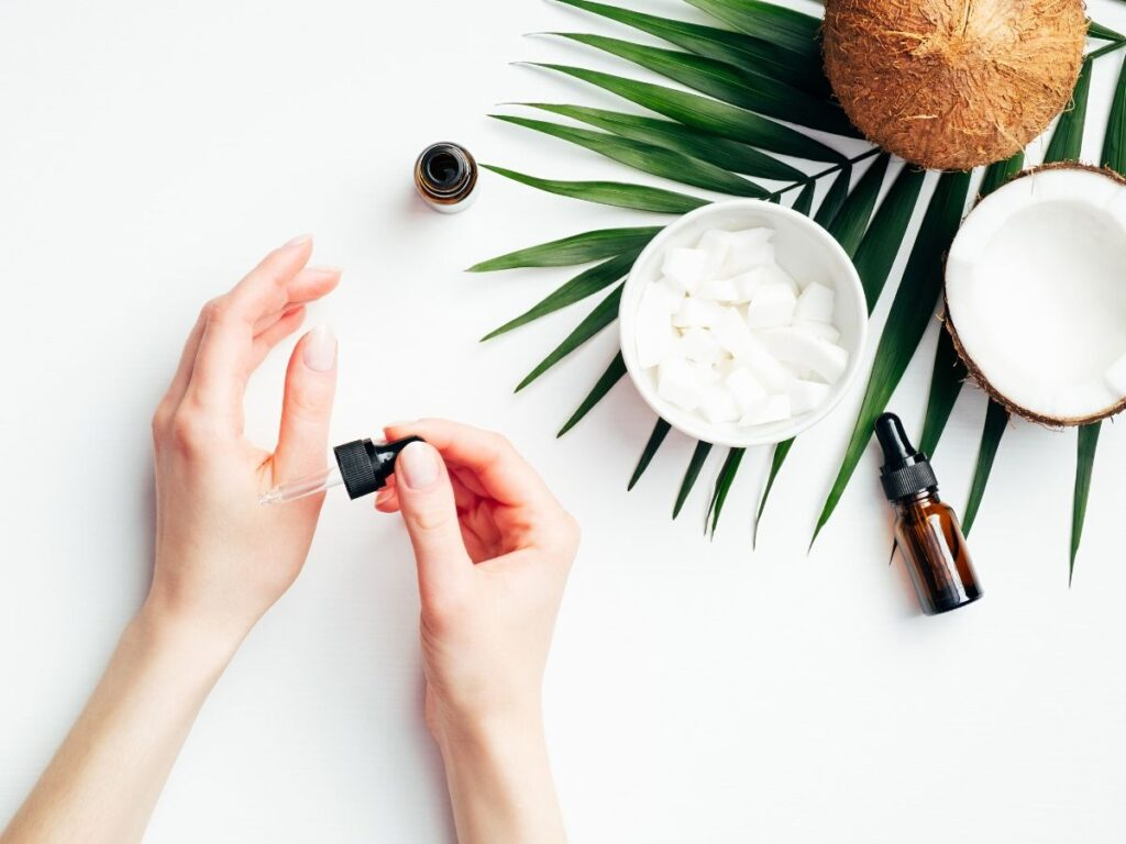 hands applying essential oil with coconut oil in background and palm leaf on table