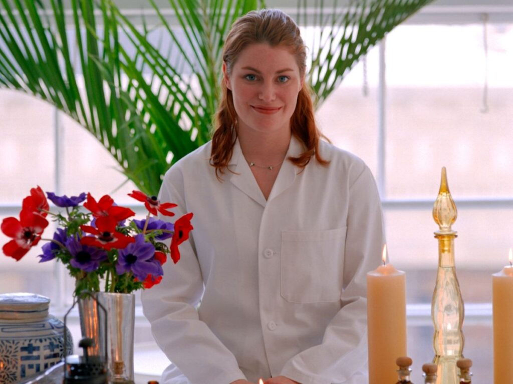 aromatherapist with candles, essential oils and flowers on a table
