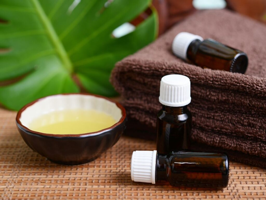 bottles of essential oils with brown towels and a small bowl of carrier oil