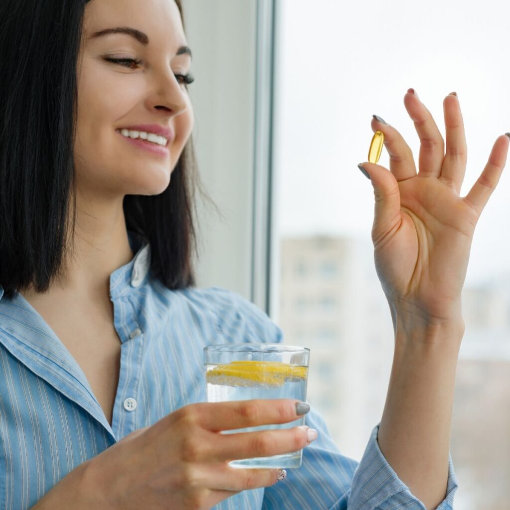 woman ingesting an essential oil veggie capsule with lemon water in her hand