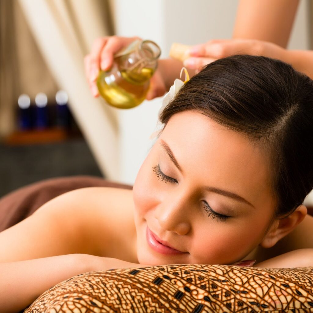 woman receiving an aromatherapy massaged with essential oils