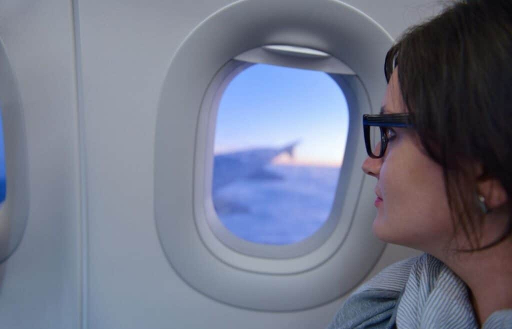 woman sitting in a window seat on airplane