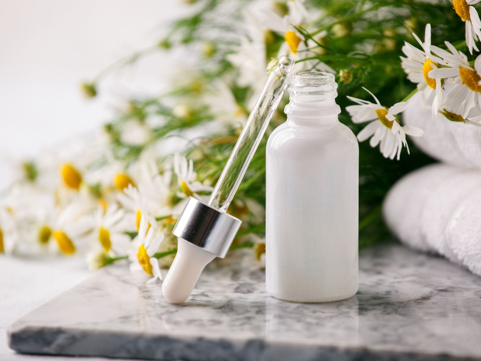 white essential oil bottle with flowers in the background.