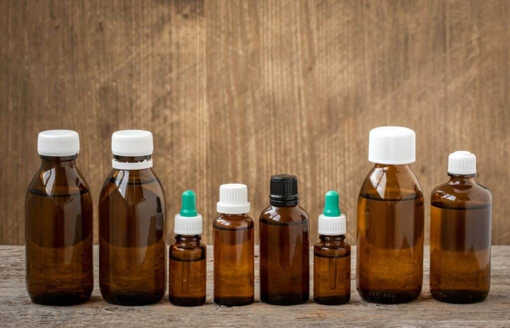 multiple amber colored essential oil bottles in different sizes on table