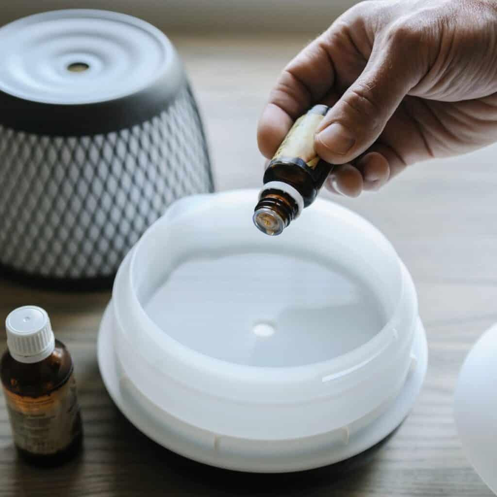 hand adding essential oils to a diffuser