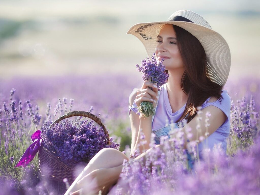 woman sitting in lavender field smelling flowers