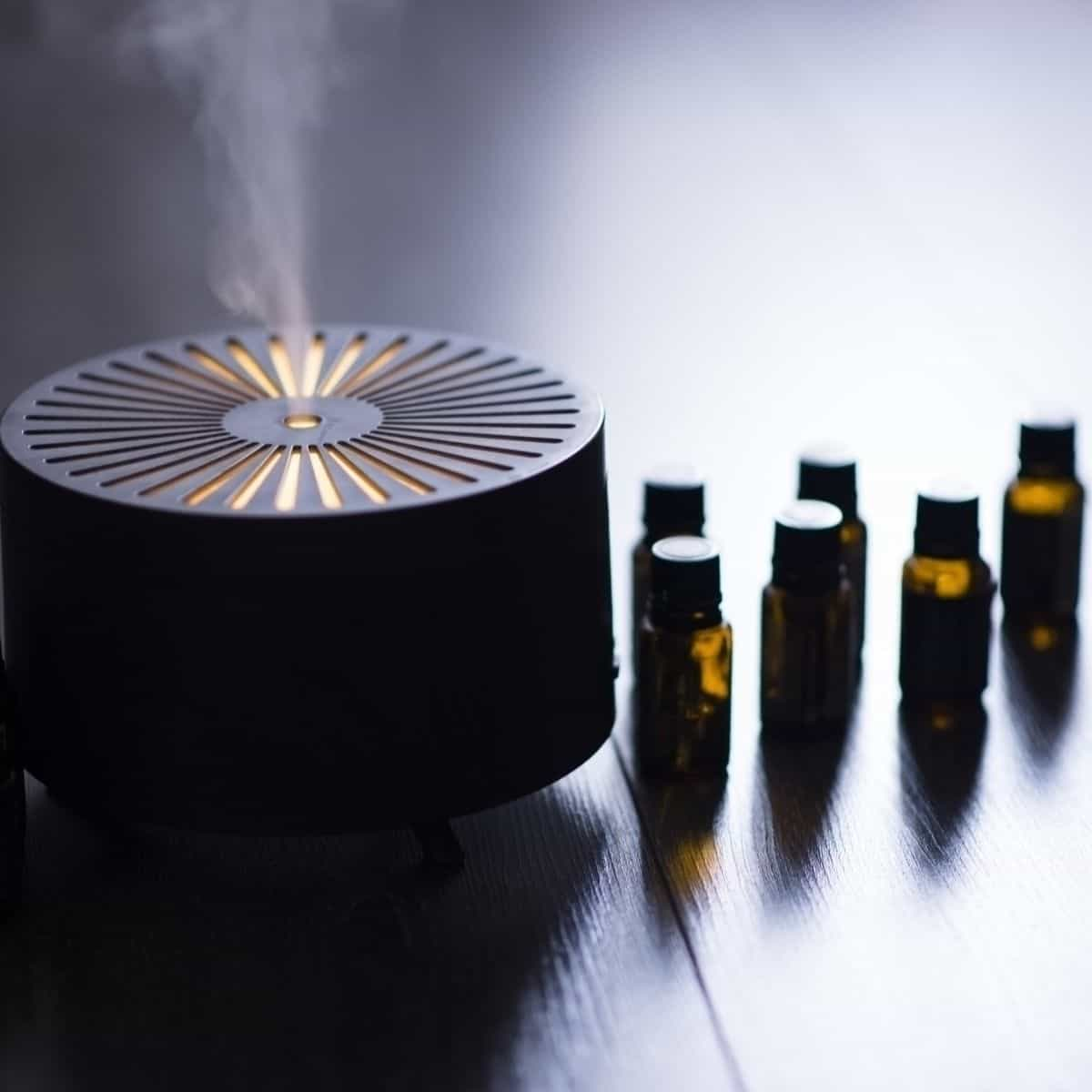 essential oil diffuser with essential oil bottles on table.