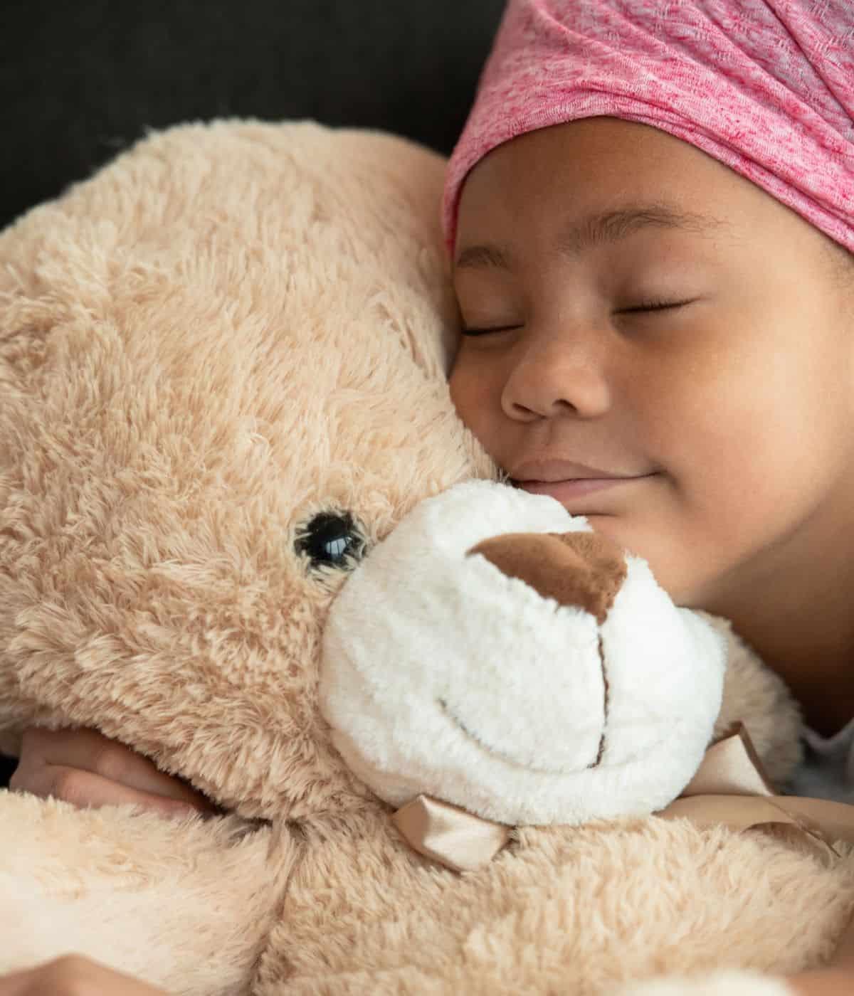 Little girl sleeping with a teddy bear stuffed animal.