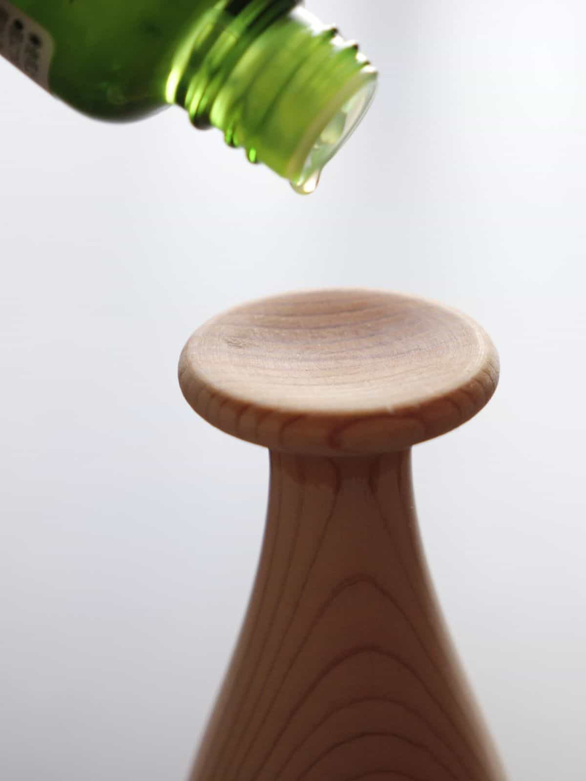 Wooden diffuser on table with essential oil dripping onto it.